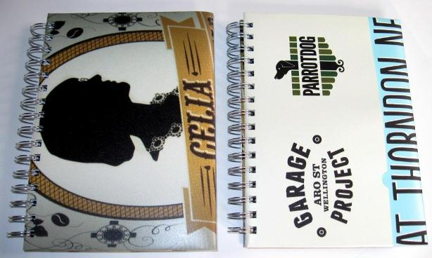 Front view of the recycled poster notebooks featuring Celia Wade-Brown Ale
