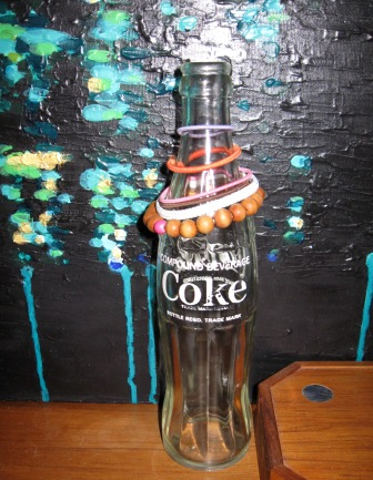 Old coke bottle used to keep hair ties at the ready with a painting by Alex Di Mecurio in the background